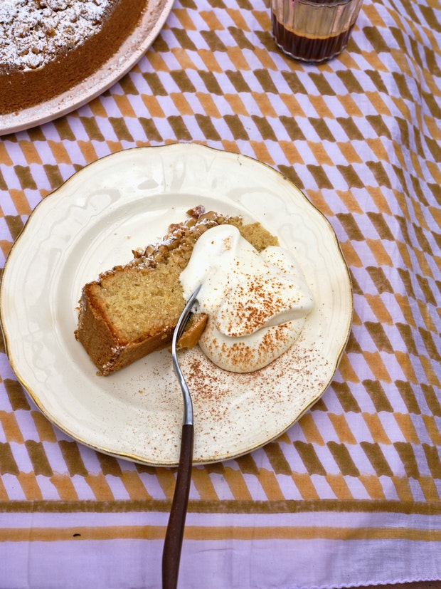 Slice of Cake with Whipped Cream on Purple Tablecloth