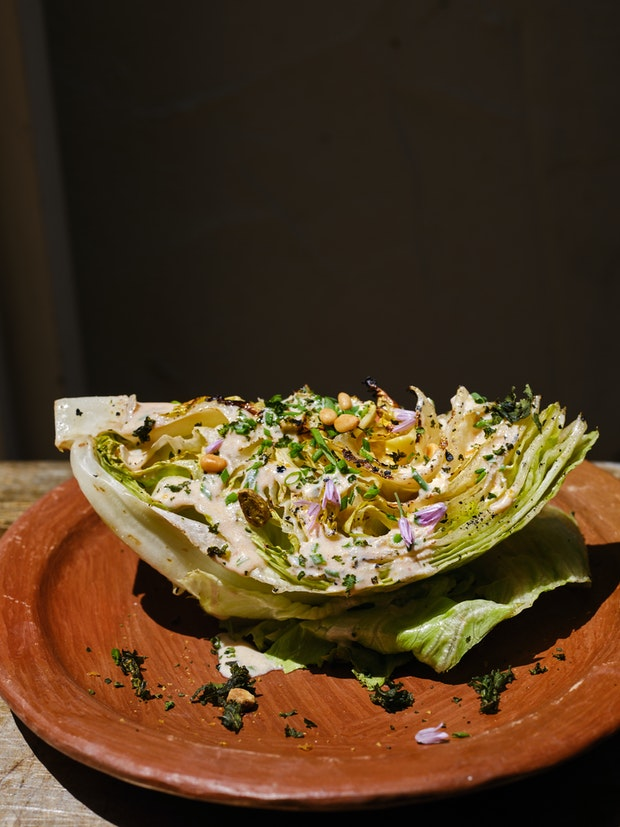 Grilled wedge salad with spicy buttermilk ranch dressing on a plate