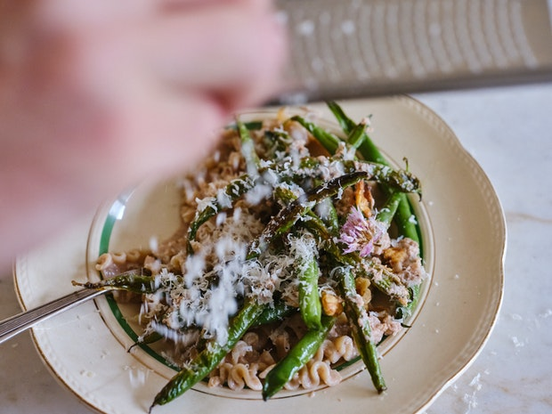 Grating Parmesan Cheese over Bowl of Blistered Green Beans