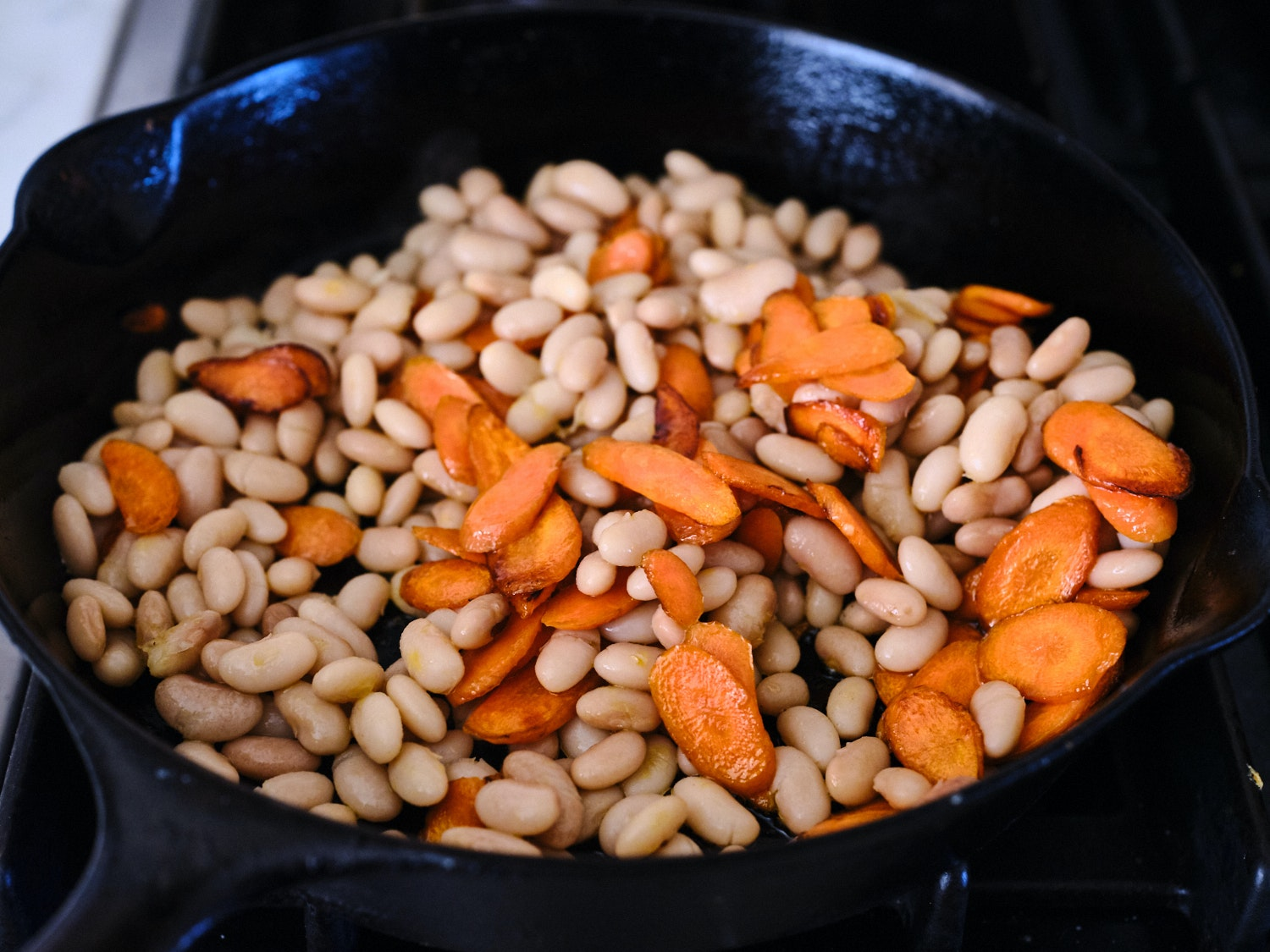 Carrots and beans in a cast iron skillet