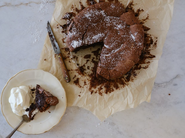 Close up photo of Flourless Chocolate Cake with a Slice Cut from It
